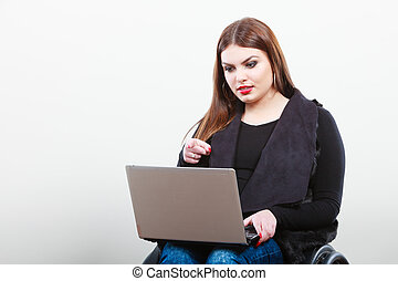 Crippled lady with laptop. Young disabled girl on...