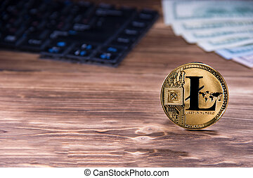 Criptocurrency concept golden litecoin coin on wooden background next to keyboard and dollars