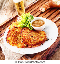 Crisp crunchy golden potato fritters served with a beer on a...