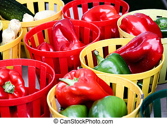 Crisp red and green peppers in colorful containters