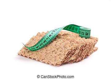crispbread with measuring tape on white background