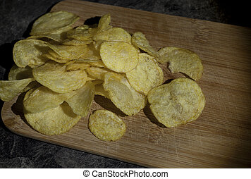 crisps - potato chips sprinkled on a wooden cutting board