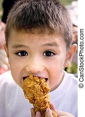Crispy Chicken - a latino boy eating a crispy chicken leg