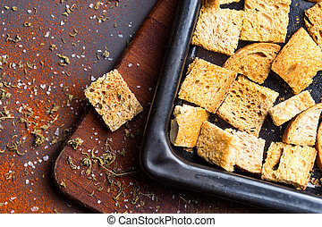 Crispy croutons with spices over wood table. Crispy croutons...