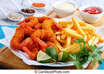 crispy crunchy parmesan bread crumbs coating Fried Shrimps with lime wedges, french fries and parsley