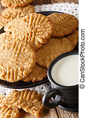 Crispy peanut butter cookies with a cup of milk close-up. vertical