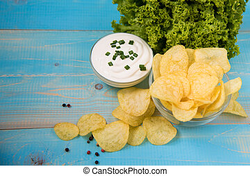Crispy potato chips in a glass bowl with sour cream