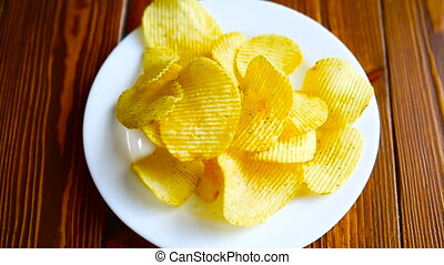 Crispy potato chips in a white plate on an old kitchen table