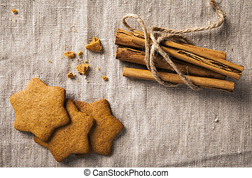 """Decorative, sparse christmas arrangement with greeting card copyspace for """"Merry Christmas""""-text. Ginger bread and cinnamon sticks arranged on brown table cloth."""