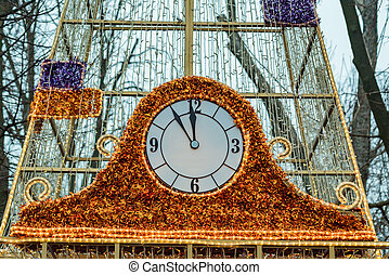 Cristmas clock outdoors decorated with tinsel close