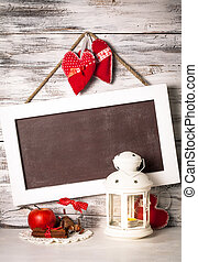 Cristmas lantern with board for greetings over shabby wooden wall
