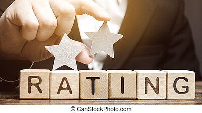 Critic puts the second star above the word Rating on wooden blocks. The concept of quality of service. Hotel or restaurant rating. Evaluation of critics and visitors. Poor quality. Negative feedback.