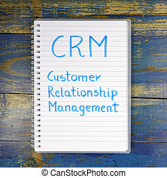 CRM- Customer Relationship Management written in notebook on wooden background