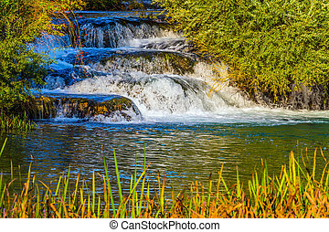 Cascade waterfalls are lit by sunset rays