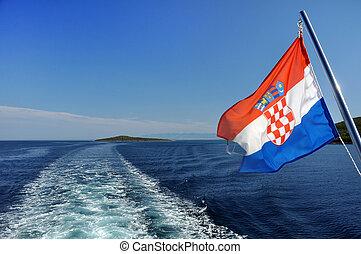 Croatian flag waving behind a passenger ship, water trail