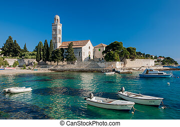 The boats in the harbour and in the back a ancient church.