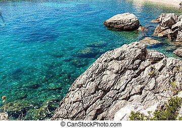 Croatian seashore. Coast of Hvar Island. Greetings from the sea. Sea and rocks in Croatia. Landscape of the Adriatic Sea. Hot summer day.