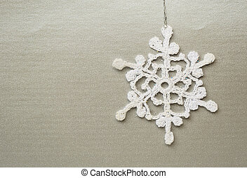 Crochet snowflake on a silver background