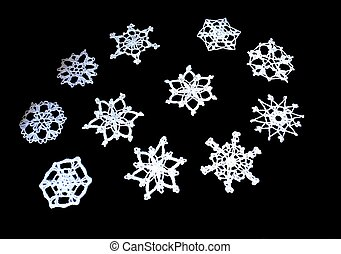 crochet snowflakes isolated against a dark background.