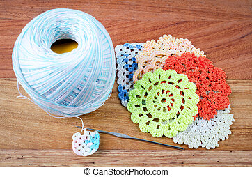 Crochet, the making of a crocheted on wood background, a retro handmade craft with balls of yarn, color blue .