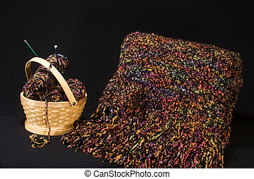 Blanket or quilt chrocheted with basket of extra yarn by its side.