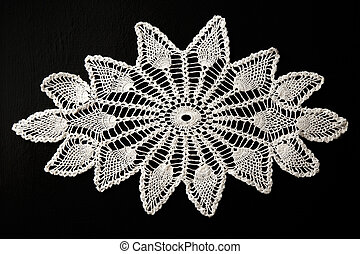 Crocheted white lace decorative napkin on black