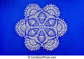 Crocheted lace napkin home decoration on blue