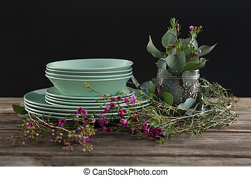Crockery and floral decorations on wooden plank - Close-up...