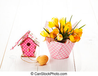 crocus flowers on white wooden background, spring decoration with easter eggs