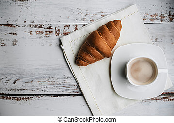 croissant and a white Cup of coffee on a wooden table on a napkin
