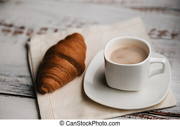 croissant and a white Cup of coffee on a wooden table