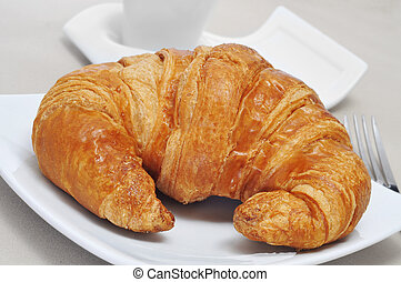 continental breakfast: cup of coffee and croissant