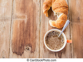 Croissant and coffee for breakfast on old wooden table