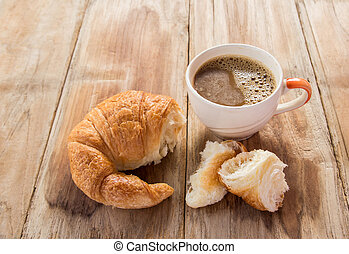 Croissant and coffee for breakfast on wooden table