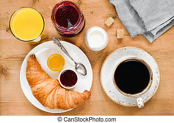 Croissant, coffee with cream, orange juice and jam on wooden table