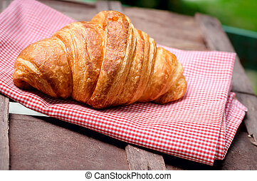 croissant on brown wood table