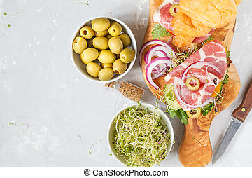 croissant sandwich with ham, olives and vegetable