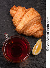 croissant with a cup of tea on a black stone background. Top view