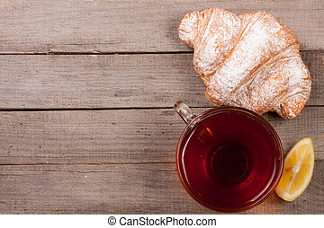croissant with a cup of tea on an old wooden background with copy space for your text.