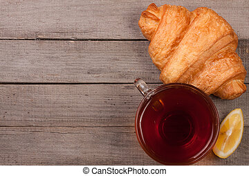 croissant with a cup of tea On an old wooden background. Top view