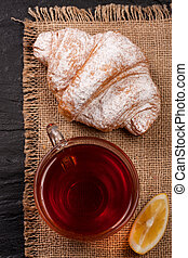 croissant with a cup of tea on sackcloth. Top view