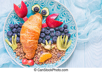 Croissant with berries for funny kids breakfast