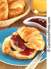 Croissant with butter and strawberry jam