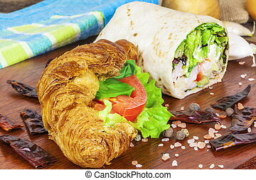 Croissant with cheese and tortilla wrap on table