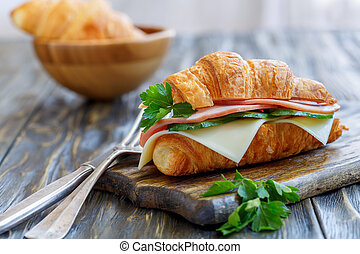 Croissant with cheese, ham and cucumber.