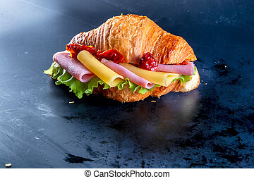 Croissant with cheese, salad, sausage and vegetables