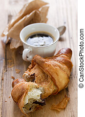 croissant with chocolate and cup of coffee