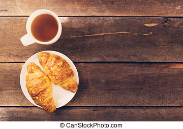 croissant with cup of tea on wooden table. copy space
