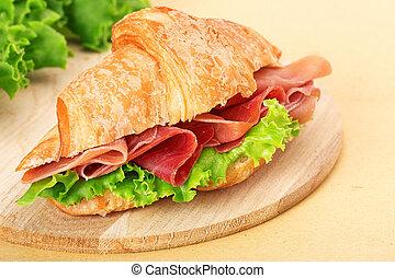 croissant with ham and lettuce on wooden chopping board