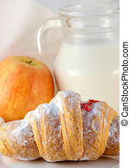 Croissant with jam and a jug of milk and an apple, a light morning meal
